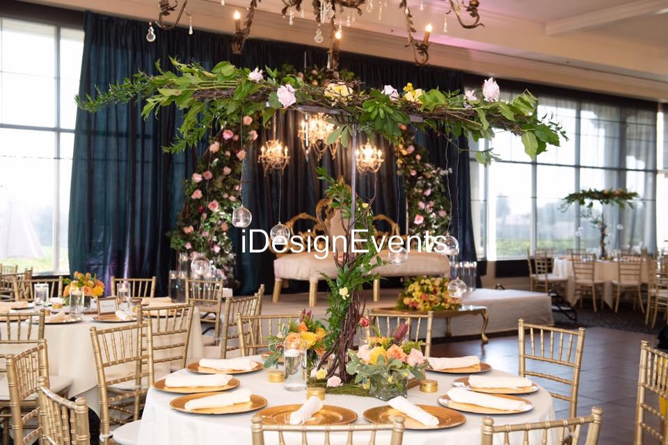 enchanted garden theme wedding reception decor arch with greenery and flowers with chandeliers and huge king loveseat forest by @idesignevents